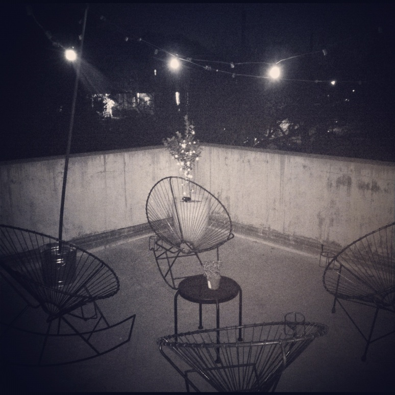 Acapulco chairs and globe lights at night